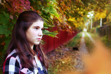 teen girl face: teen girl with long brown hair sad portrait on the autumn fall background Stock Photo