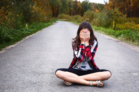 shy girl: beautiful  teen girl sit on the country empty road