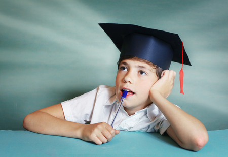 prodigy: preteen handsome boy in graduation cap think about school subject