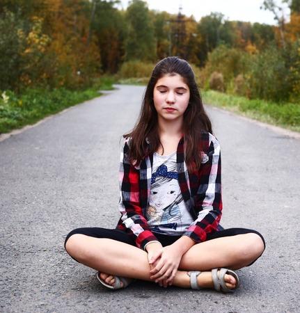 pubertad: hermosa muchacha adolescente se sienta en la carretera vacía país