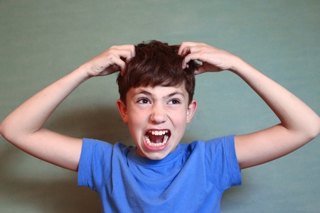 preteen handsome boy scratch his head isolated on blue Archivio Fotografico