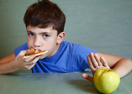 refuse: teen handsome boy with pizza refuse to eat apple Stock Photo