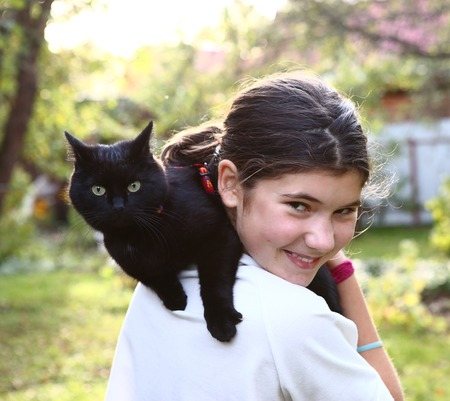 beautiful teenager girl in white t-shirt hold black cat on her shoulder Stock Photo