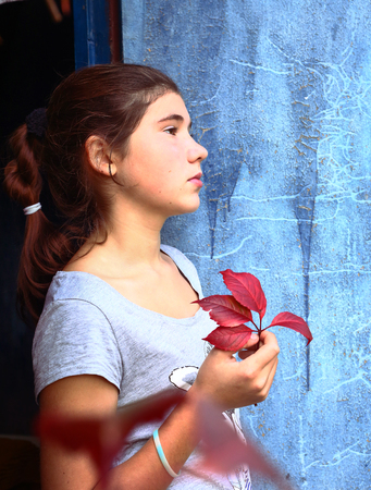 teenager sad girl portrait with red grapes leaf and shabby blue door