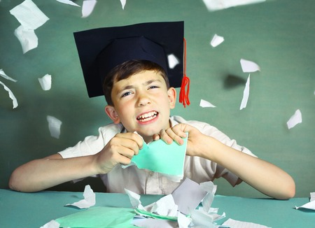 demotivated: preteen handsome boy in graduation cap  tear his copycook for pieces Stock Photo