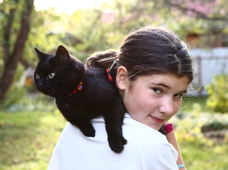 burmese: beautiful teenager girl in white t-shirt hold black cat on her shoulder Stock Photo