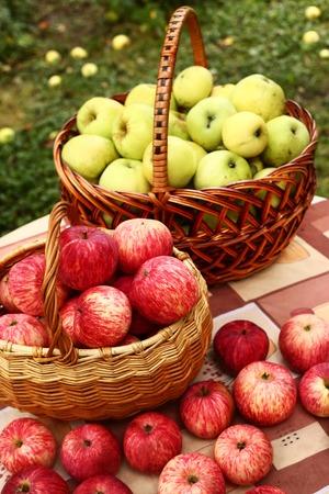 manzana: roja madura fresca cortó las manzanas en la cesta sobre la mesa Foto de archivo