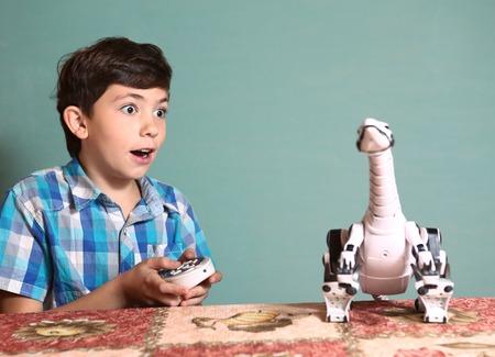 ni�o modelo: preadolescente juego chico guapo con el juguete de dinosaurio por pult control remoto