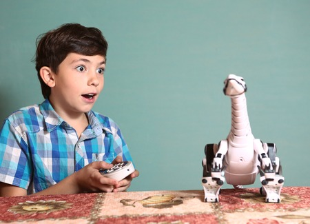car model: preteen handsome boy play with dinosaur toy by remote control pult Stock Photo