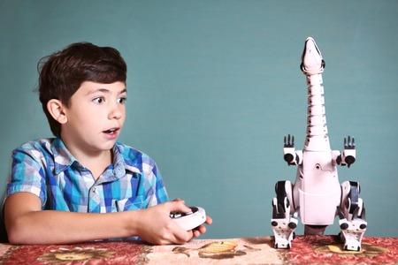 niño saltando: preadolescente juego chico guapo con el juguete de dinosaurio por pult control remoto