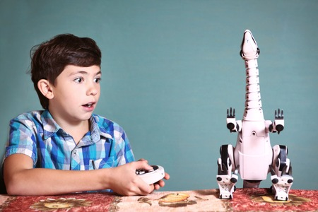 preteen boy: preteen handsome boy play with dinosaur toy by remote control pult Stock Photo