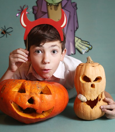 funny boy: preteen handsome boy with pumpkins and red horn celebrate halloween