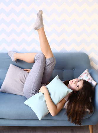 in pajama: teen pretty girl with long dark hair lay on the sofa in pajamas with pillows Stock Photo
