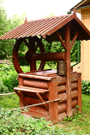 well made: wooden rural water well made from log with roof and wheel