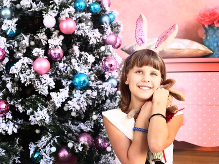 beautiful teen: teen beautiful girl in pink woolen dress with christmas decoration and tree on shabby chick room background Stock Photo