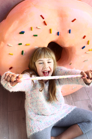 preteen: preteen blond girl in confectionery world with ginger man and donut on the background