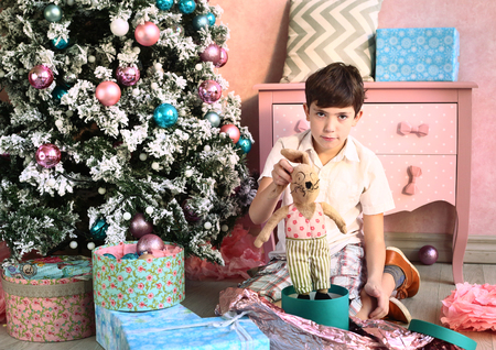 decorate: preteen handsome boy with christmas tree and presents