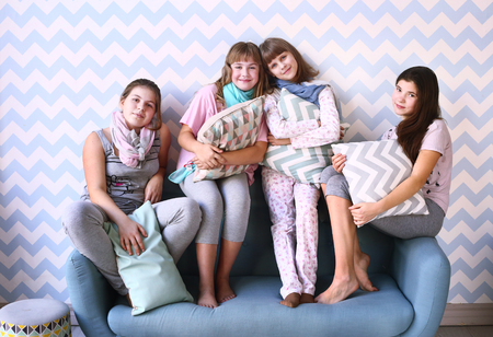 playing on divan: teen four girls on pajama party with pillows
