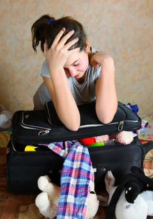 teenager girl put clothes in the case tired