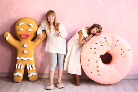 child model: happy preteen girls in confectionery designed room with marshmallow rope