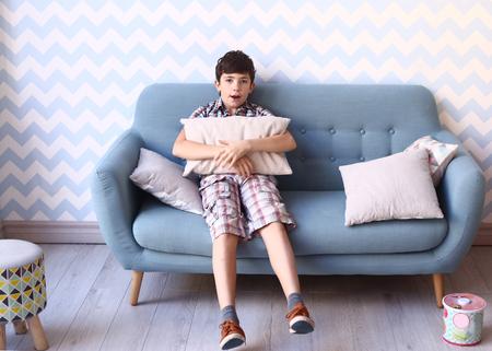 pijamada: niño preadolescente en el acogedor entre dormitorio con almohadas y un sofá