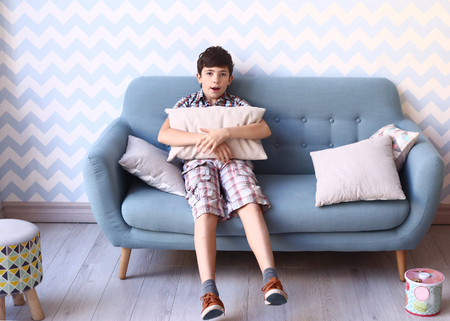 playing on divan: preteen boy in cozy bedroom interior with pillows and sofa Stock Photo