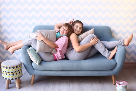 playing on divan: two happy teenager blond sister in pajamas on the sofa with pillows in the cozy design bedroom interior