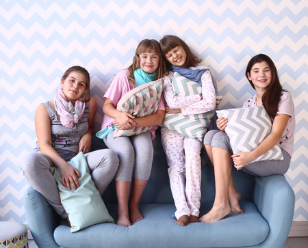 playing on divan: teenager girls in pajamas with pillows on the sofa