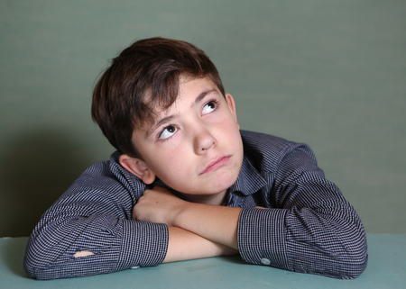 preteen boys: preteen schoolboy close up thinking portrait with hands on blue wall background