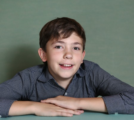 preteen boys: preteen handsome boy smiling portrait on blue wall background