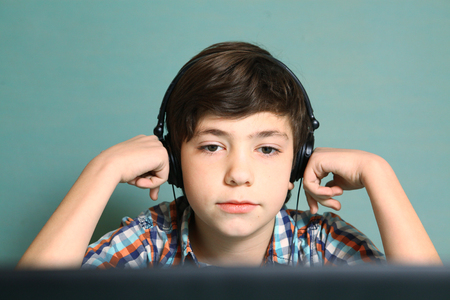 asian youth: preteen handsome boy with headphones listen to popular mp3 music on computer close up expression portrait isolated on blue