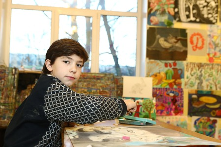 trimester: MOSCOW, DECEMBER  24, 2015: Unidentified art school student boy participate in final  painting exhibition at the end of school trimester in Russia Moscow, December 24, 2015