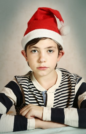 elf's: funny close up portrait of a preteen boy in santa hat representing chrisrmas elf with grimace  and protruding ears