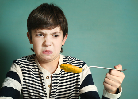 preteen handsome boy with tablespoon of pumpkin soup refuse to eat disgust grimace
