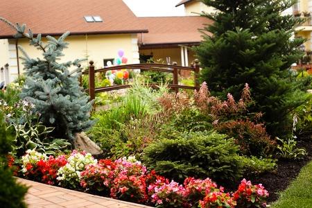 Mooie tuin met vuren blauwe boom flowerbed en houten breuk met rode pannendak herenhuis op de achtergrond