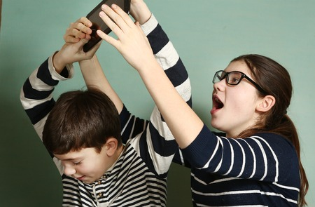 teen siblings couple brother and sister in glasses fighting because of tablet try to take it for gaming Stock Photo