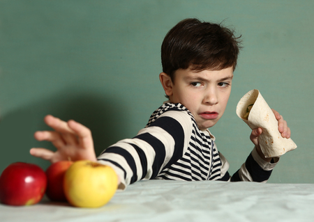 preteen handsome boy want to eat fast food caesar roll and  refuse eating fresh apples Stock Photo