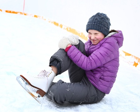 teen legs: teen skater girl in down jacket and knitted blue hat fall down on skating rink hit her leg and grimace with pain