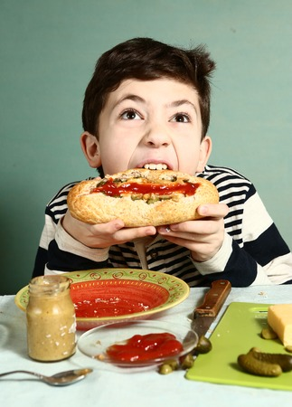 hotdog sandwiches: preteen handsome boy cook by himself big hotdog from french baguette sausage cucumber cheese ketchup and mustard and make big bite Stock Photo