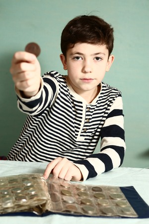 numismatic: boy preteen numismatic collector show his coin with hole in the middle look through it close up portrait Stock Photo