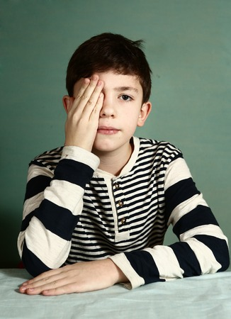 one eye: preteen handsome boy under ophthalmologist examination close one eye with his palm try to read letters Stock Photo