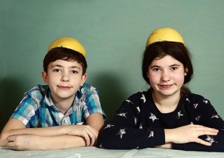 citrus family: creative kids teenage siblings brother and sister laughing peeling grape fruit make funny hat from it
