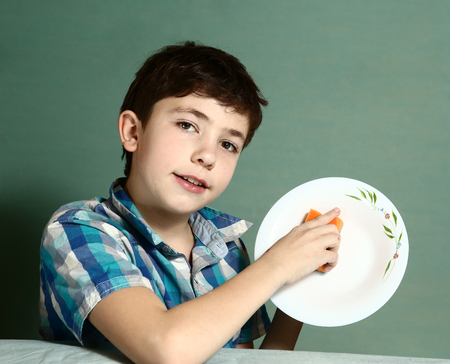 preteen handsome boy wash plate to help his mother close up portrait