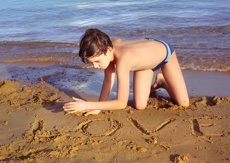 sun bathing: boy on the beach take sun bathing play with sand write love word  enjoy vacation on the sea background