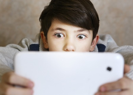 preteen handsome boy with bad gaming habit play computer game on his tablet close up portrait
