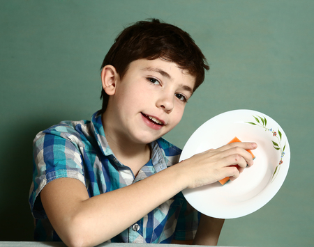 wash dishes: happy preteen boy wash dishes close up portrait on blue wall background