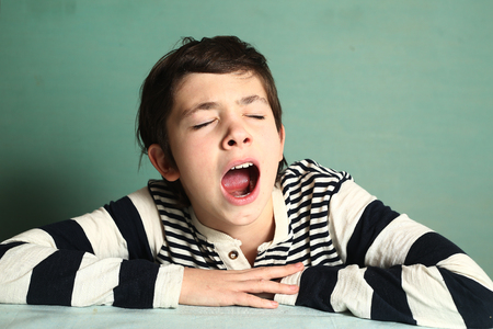 preteen handsome boy close up yawning portrait