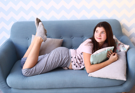 playing on divan: teenage pretty girl with long dark hair in pajamas lay on sofa with pillows Stock Photo