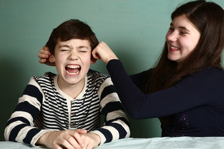 bet: teenager sister pull her brother boy ears because of the lost bet Stock Photo