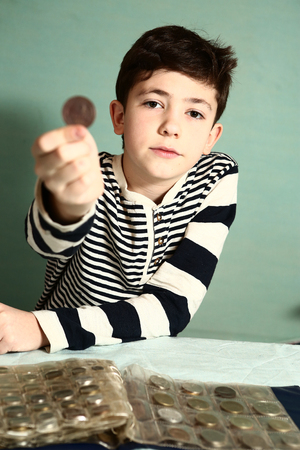 numismatic: boy preteen numismatic collector show his coin collection